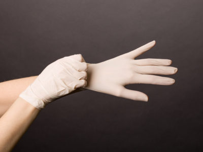 Female hands putting on latex gloves